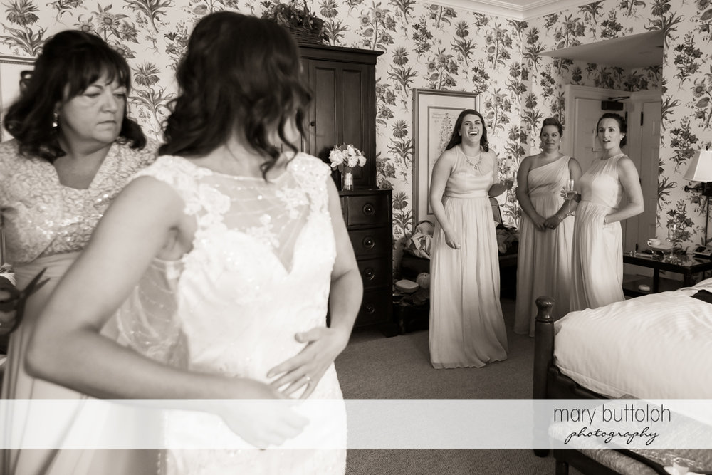 Bride talks to her bridesmaids while suiting up for the wedding at the Inns of Aurora Wedding