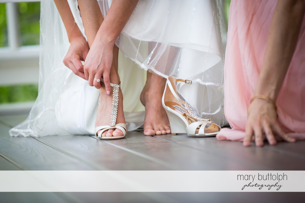 Bride puts on a shoe at the Inns of Aurora Wedding