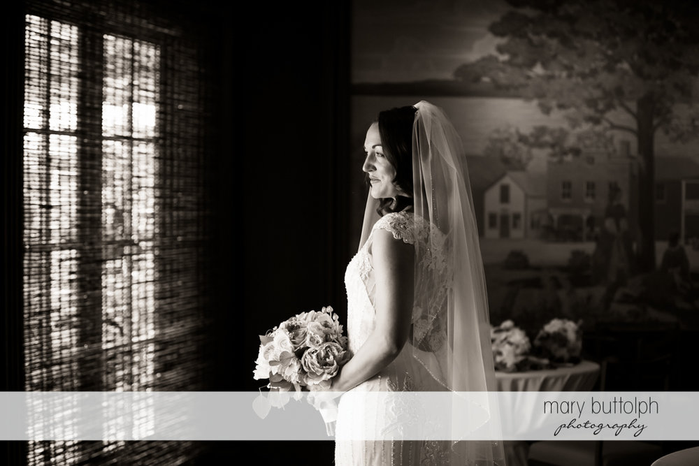 Bride poses in front of the window at the Inns of Aurora Wedding