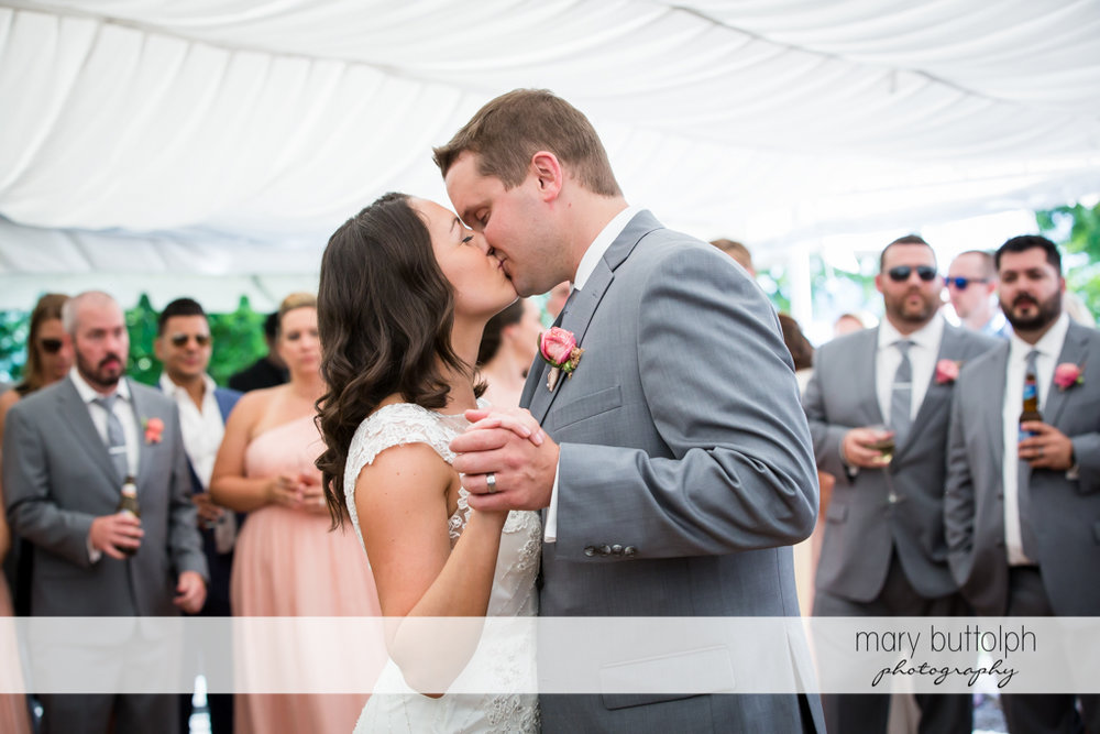 Couple kiss in the wedding tent in front of guests at the inns of Aurora Wedding