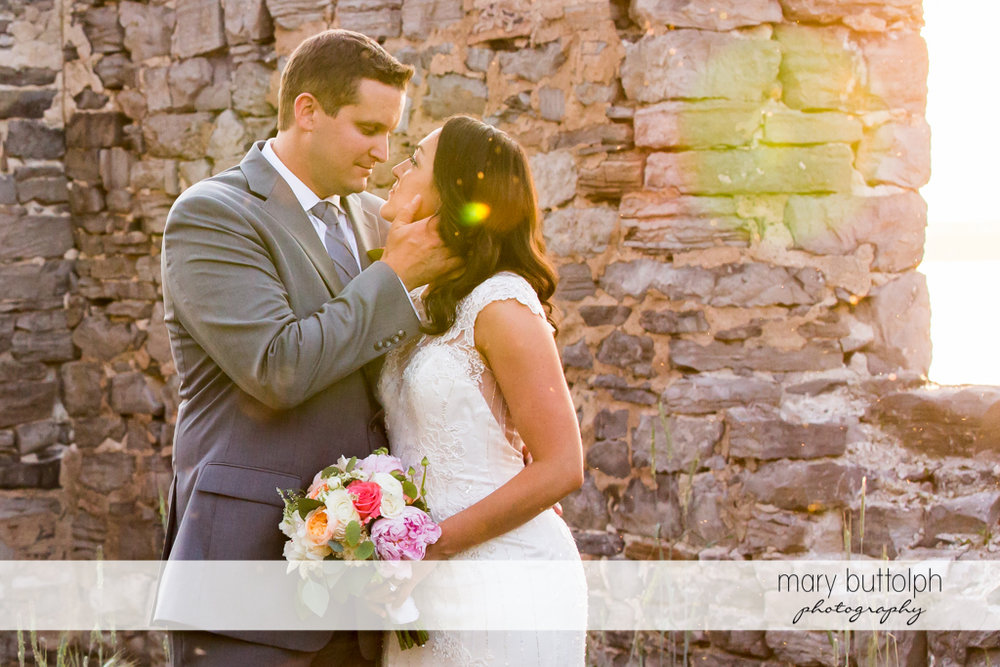 Couple in a romantic mood in front of a brick wall at the Inns of Aurora Wedding