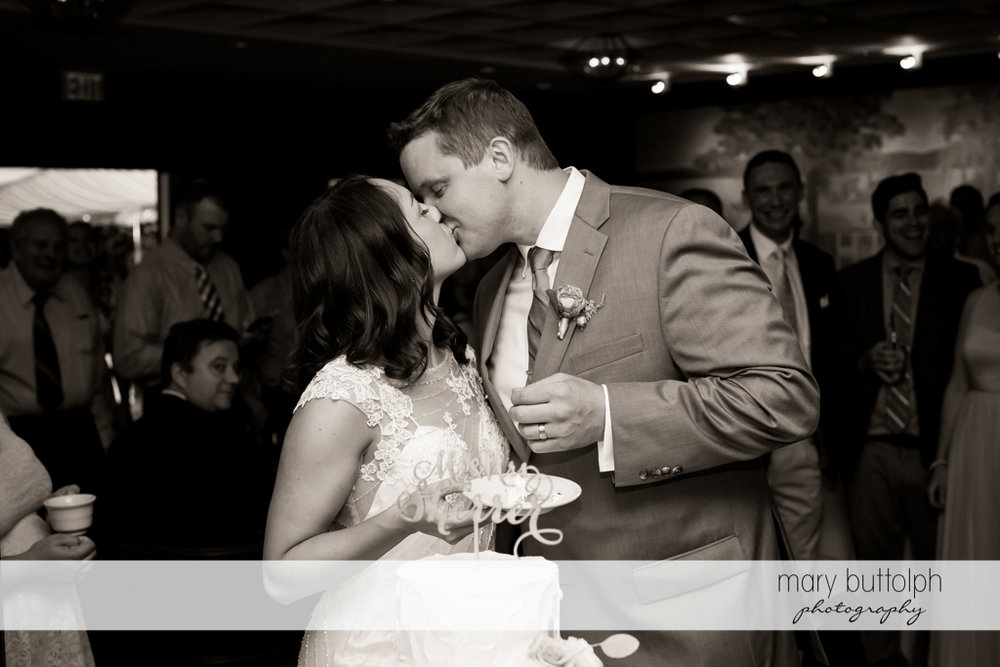 Couple kiss in front of their cake at the Inns of Aurora Wedding