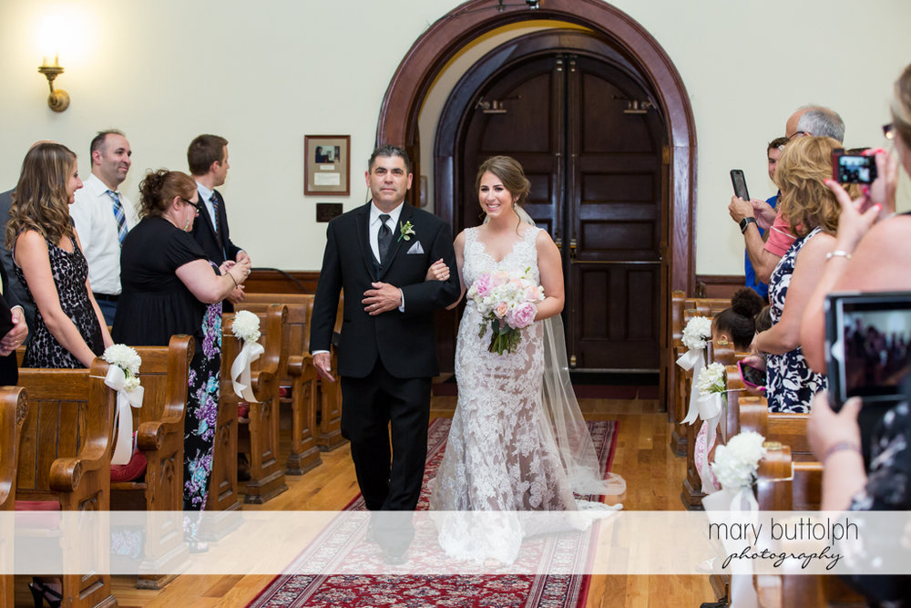 Couple approach the altar as guests look on at The Lodge at Welch Allyn Wedding