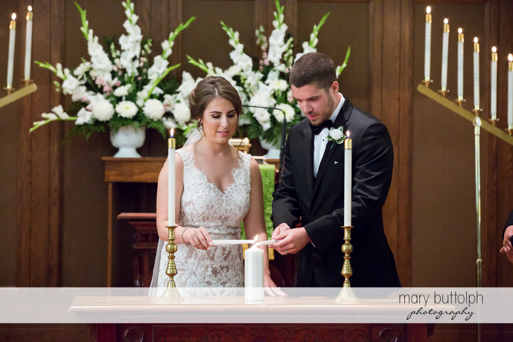 Couple light a candle during the wedding ceremony at The Lodge at Welch Allyn Wedding