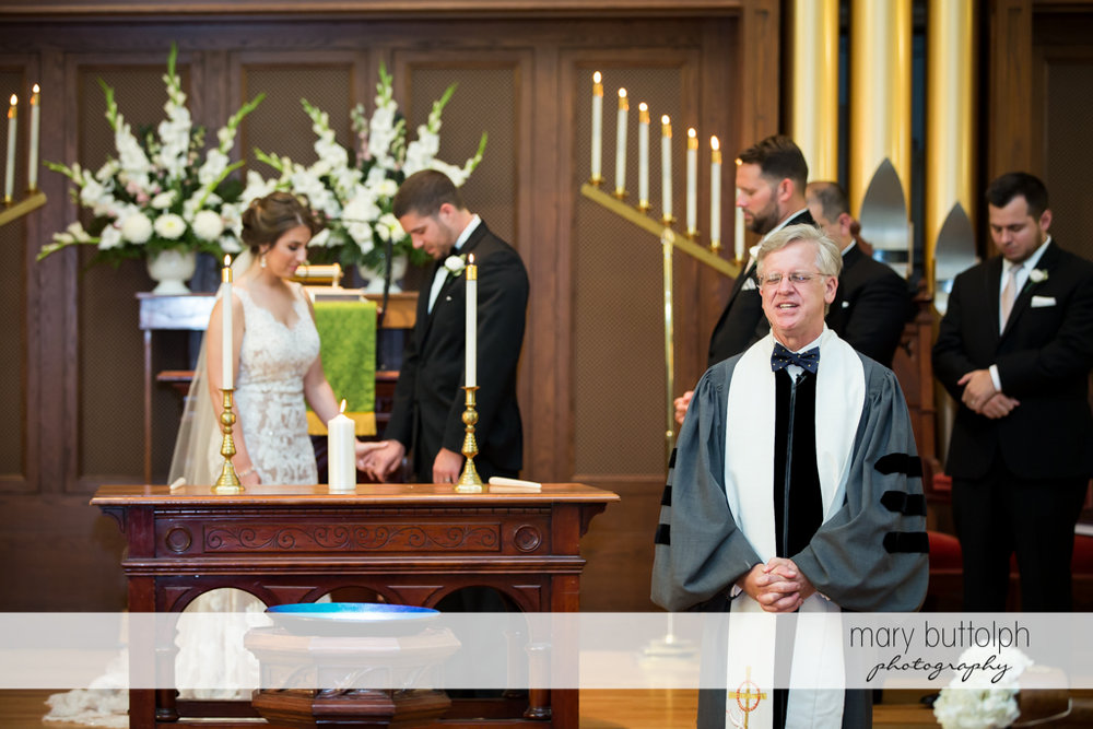 Couple stand in front of the altar as the priest addresses the audience at The Lodge at Welch Allyn Wedding