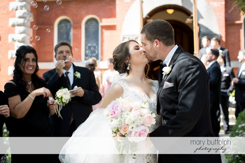 Couple kiss as they are showered with bubbles by guests at The Lodge at Welch Allyn Wedding