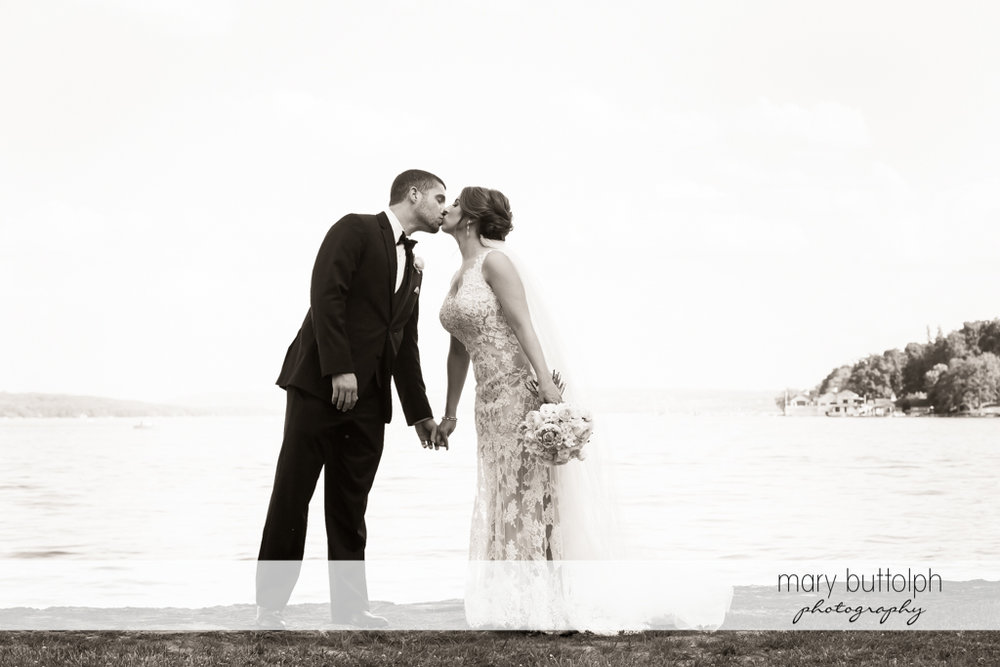Couple kiss by the lake at The Lodge at Welch Allyn Wedding
