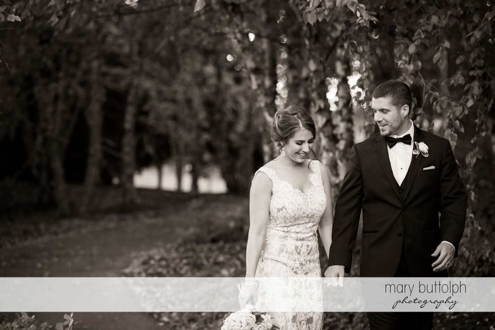 Couple stroll in the garden at The Lodge at Welch Allyn Wedding