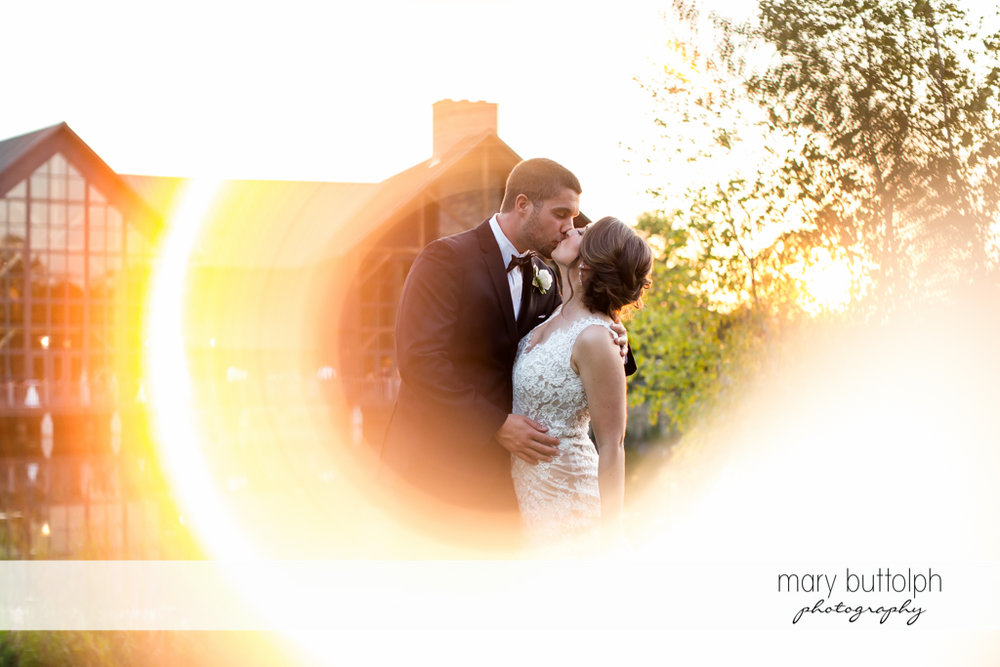 Couple kiss under the sun at The Lodge at Welch Allyn Wedding