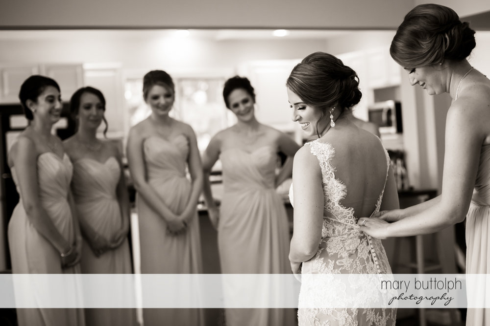 One of the bridesmaids adjusts the bride's wedding dress at The Lodge at Welch Allyn Wedding