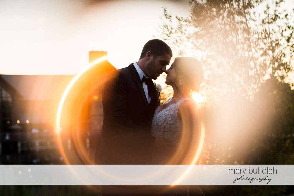 Couple rub noses as the sun sets in the garden at The Lodge at Welch Allyn Wedding