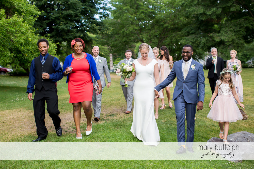 Couple and their family stroll in the garden at the Inns of Aurora Wedding
