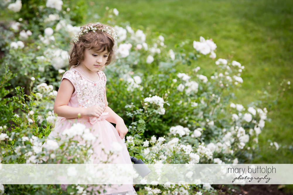 Flower girl surrounded by flowers in the garden at the Inns of Aurora Wedding