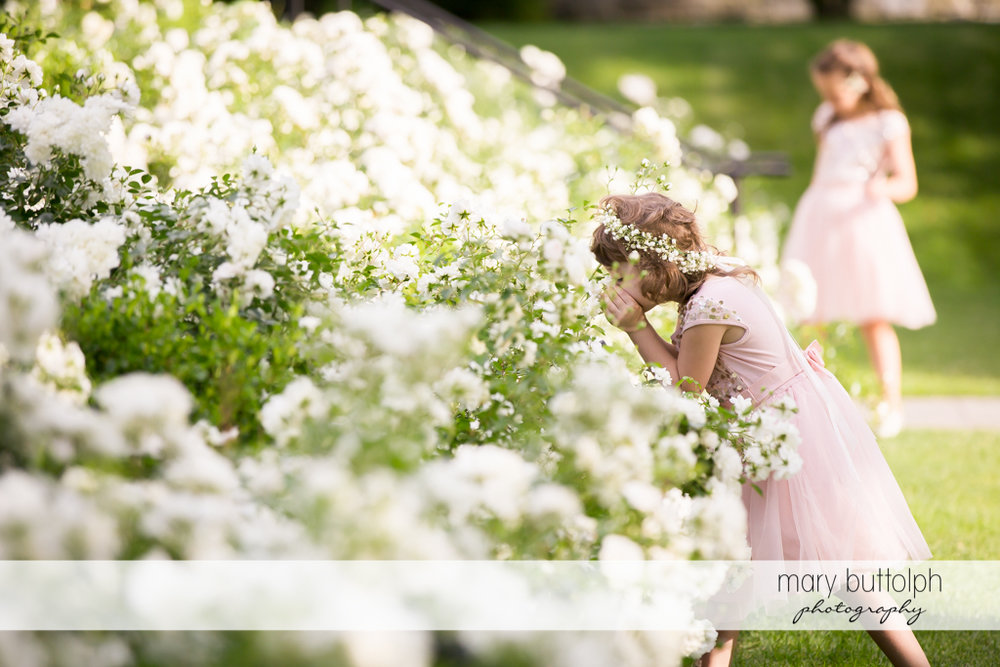 Girl whispers to the flowers in the garden at the Inns of Aurora Wedding