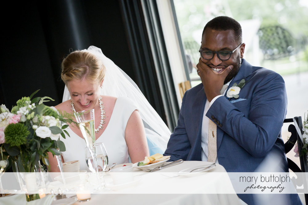 Couple share a light moment while dining at the Inns of Aurora Wedding