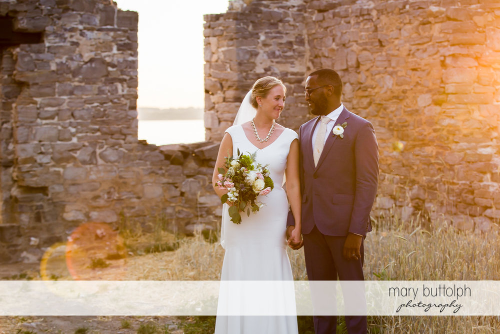 Couple pose in front of a brick structure at the Inns of Aurora Wedding