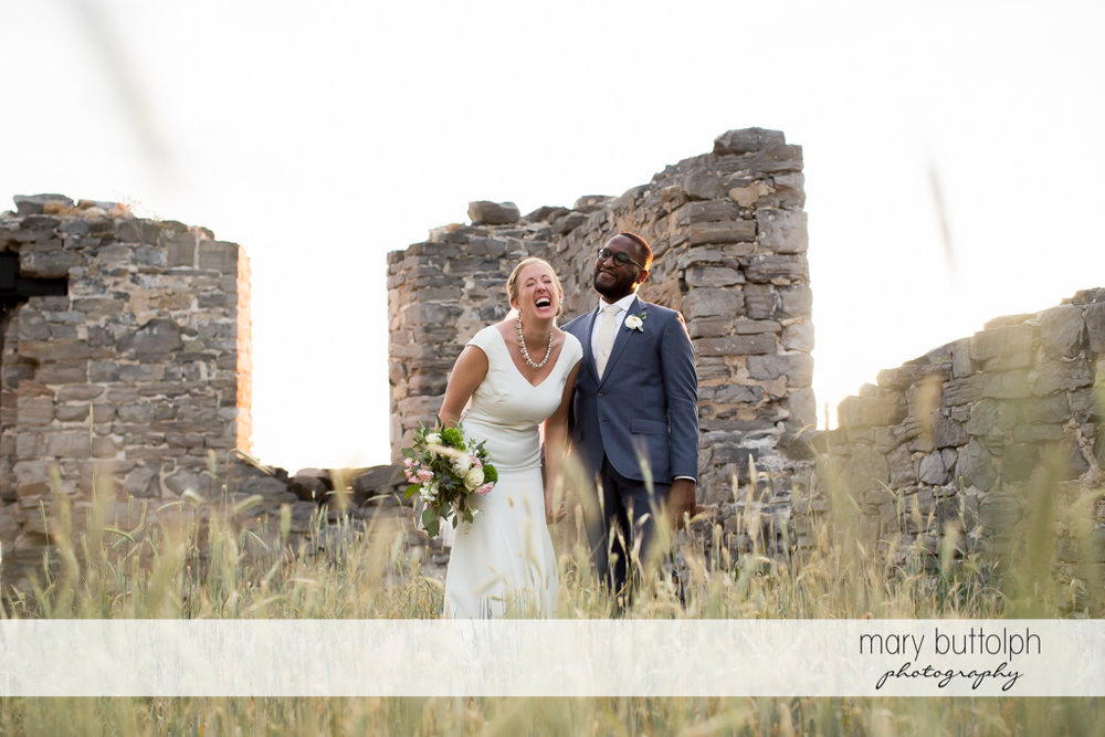 Couple share a good laugh in front of a brick structure at the Inns of Aurora Wedding