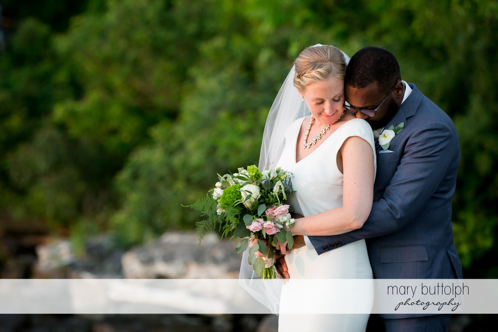 Couple show their affection in the garden at the Inns of Aurora Wedding