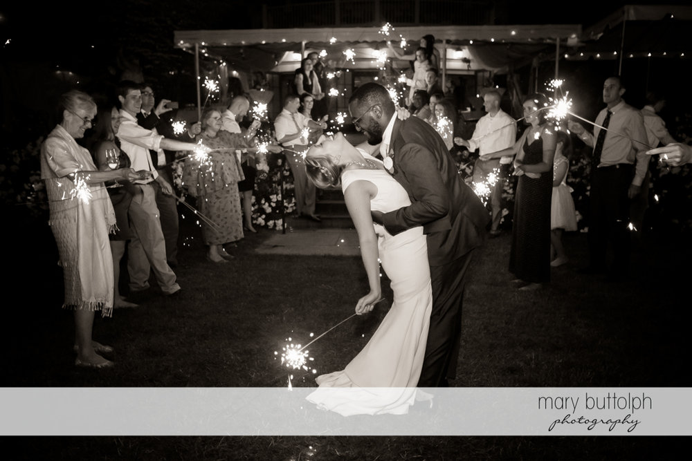 Couple and guests light up the night sky with sparklers at the Inns of Aurora Wedding