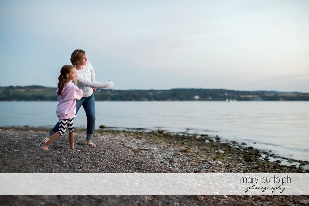 Woman and girl hone their stone skipping skills at the lake at Skaneateles Lake Vacation