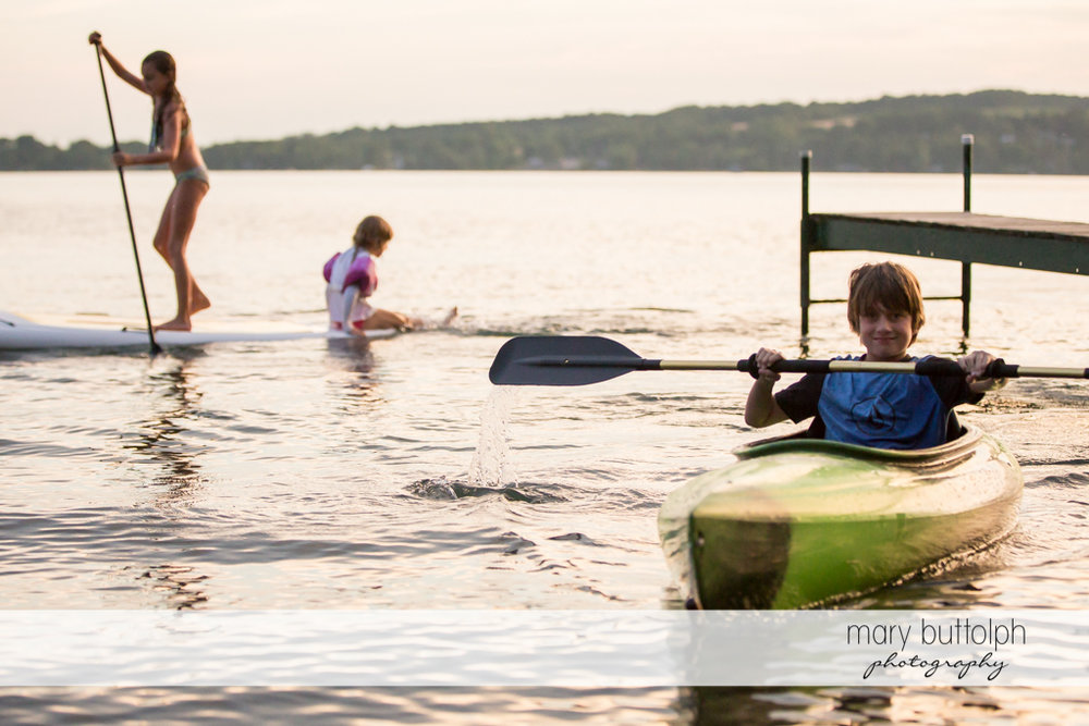 Kids use their surfboard and canoe on the lake at Skaneateles Lake Vacation