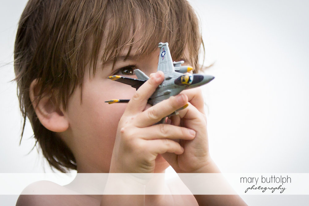 Boy plays with his fighter jet toy at Skaneateles Lake Vacation