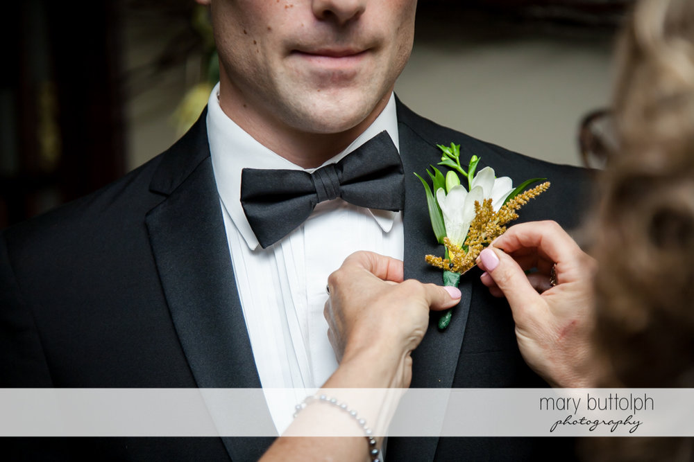 Groom gets a boutonniere at Genesee Grande Hotel Wedding