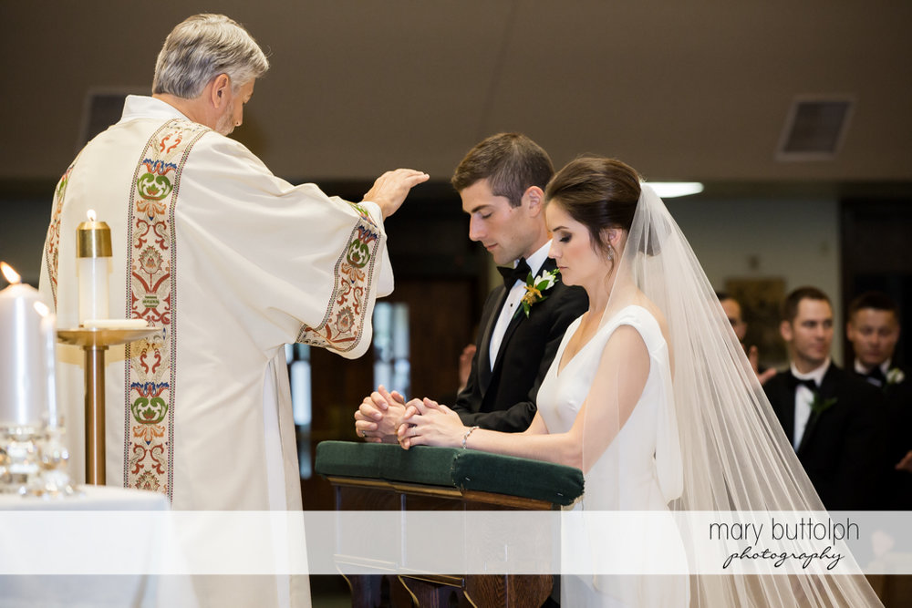 Couple are blessed by the priest at Genesee Grande Hotel Wedding