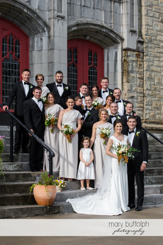The wedding party pose outside the church at Genesee Grande Hotel Wedding