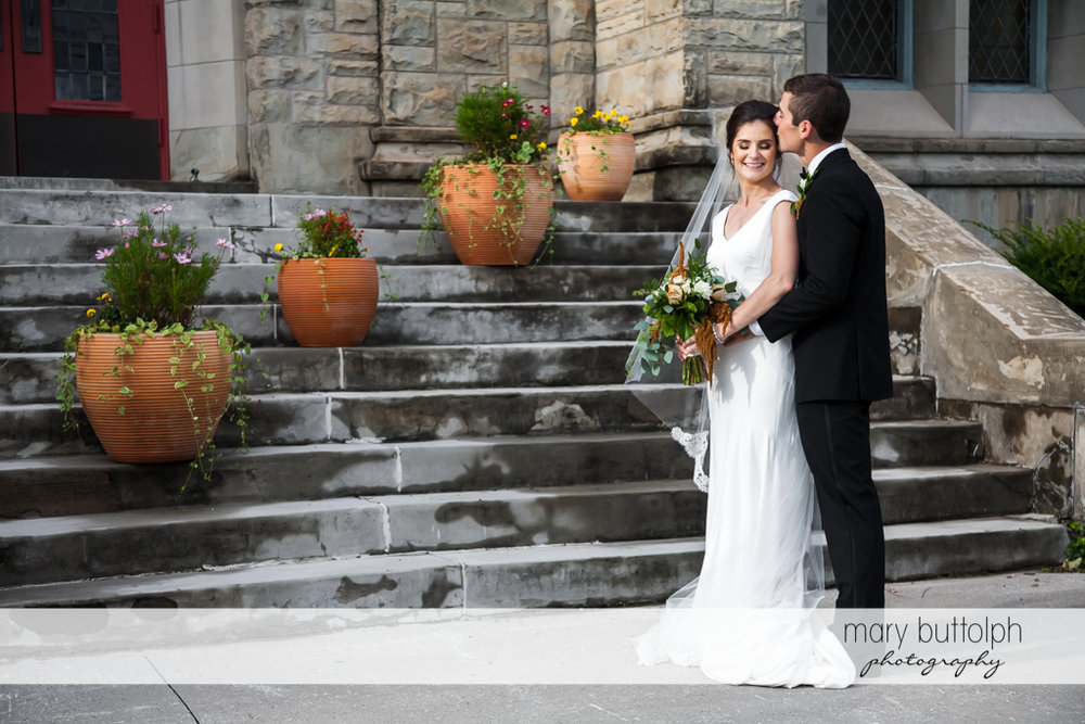Couple stand in front of the church steps at Genesee Grande Hotel Wedding