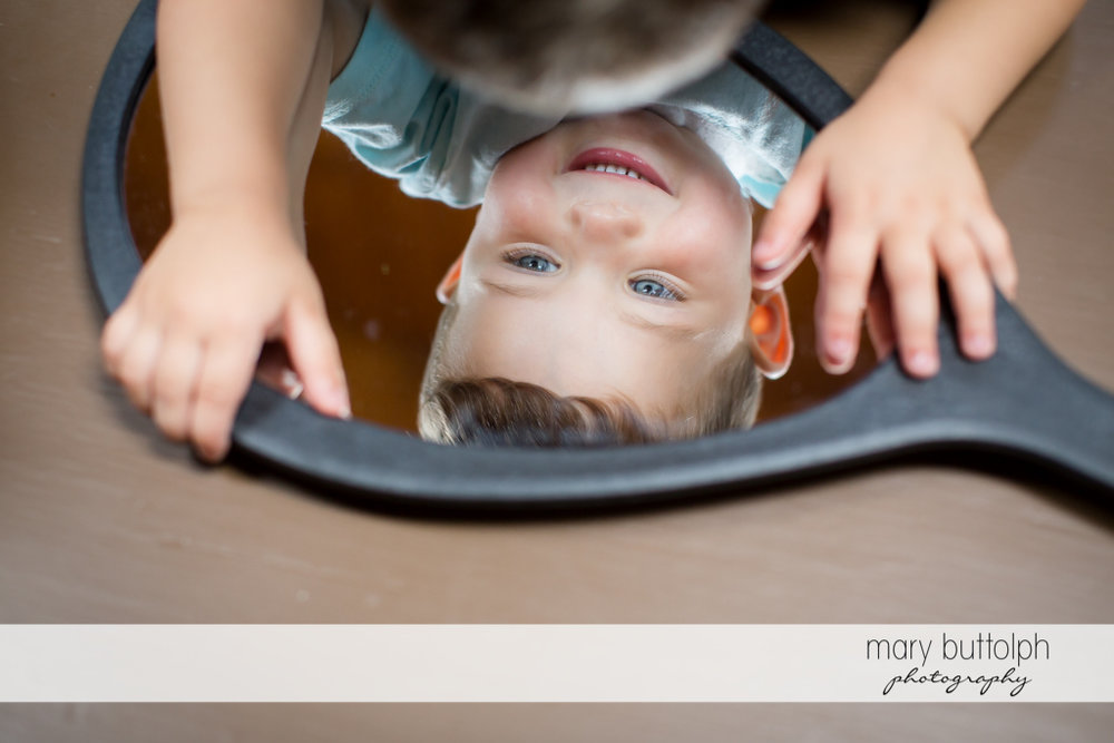 Boy plays with the mirror at Genesee Grand Hotel Wedding