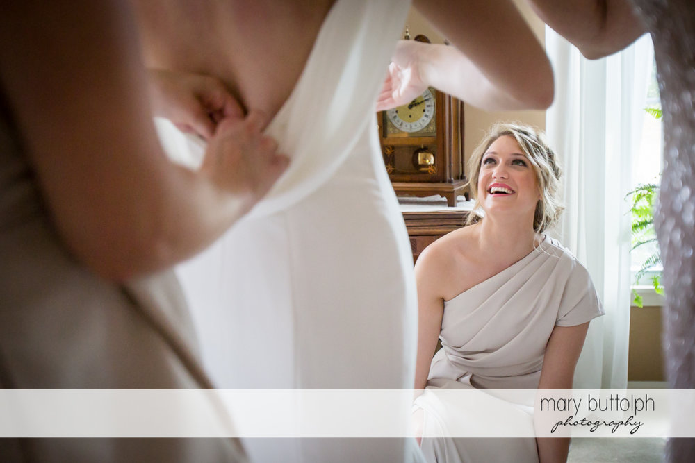 Bride's friend watches as the lucky lady prepares for the wedding at Genesee Grande Hotel Wedding