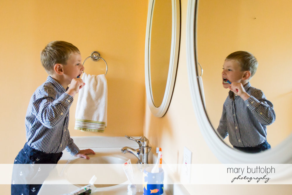 Boy brushes his teeth in front of the mirror at Skaneateles