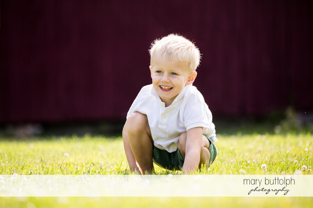 Boy squats in the garden in front of his home at Skaneateles