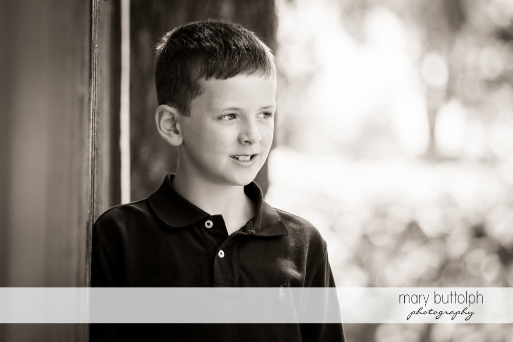 Boy poses in front of his home at Skaneateles