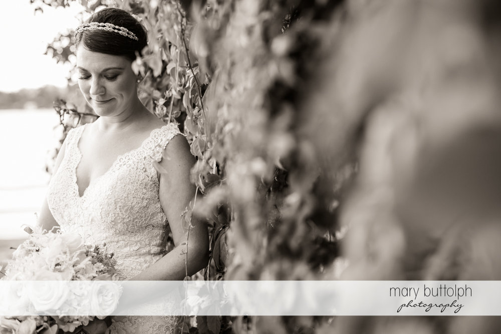 Bride in dramatic black and white shot leans on a stone wall at The Sherwood Inn Wedding