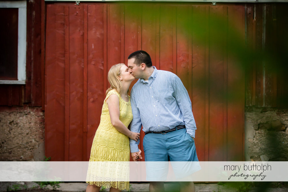 Couple kiss in front of a barn in Syracuse Engagement