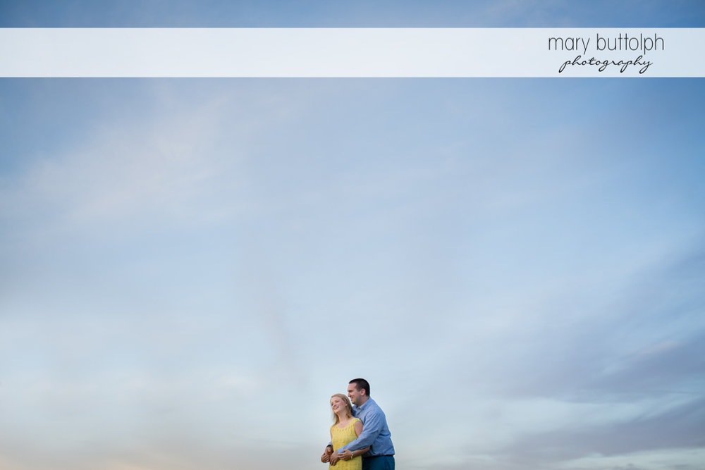 Couple are dwarfed by the clear blue sky at Syracuse Engagement