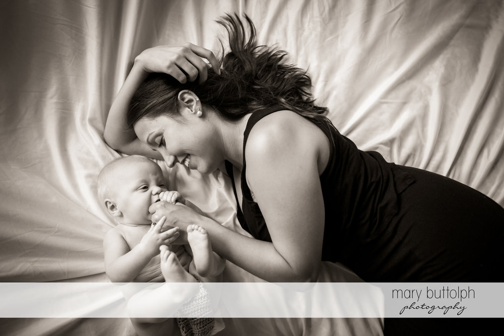 Mother and baby play in bed at Skaneateles Family