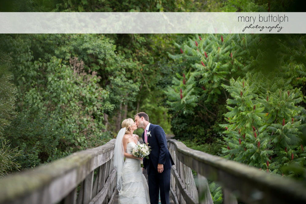 Couple kiss on the wooden bridge at Skaneateles Country Club Wedding