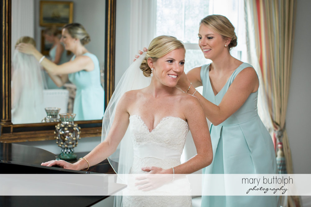 Bride gets ready for the big day with a little from help from a friend at Skaneateles Country Club Wedding