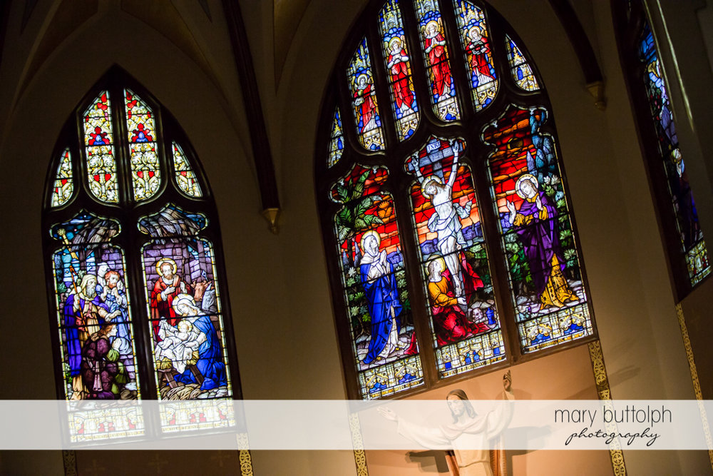 Church's stained glass windows depict the birth and crucifixion of Christ at Skaneateles Country Club Wedding