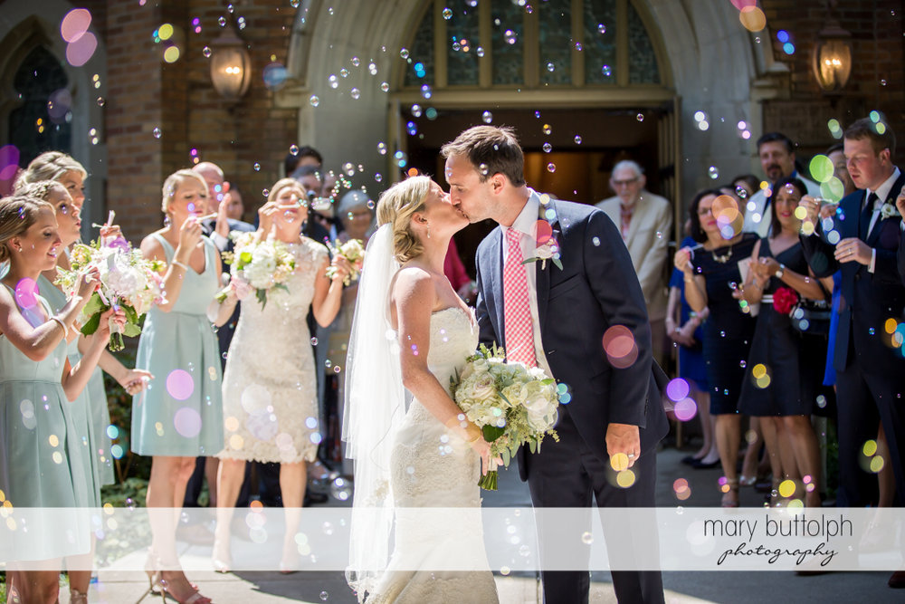 Couple kiss as they are showered with bubbles in front of a church at Skaneateles Country Club Wedding