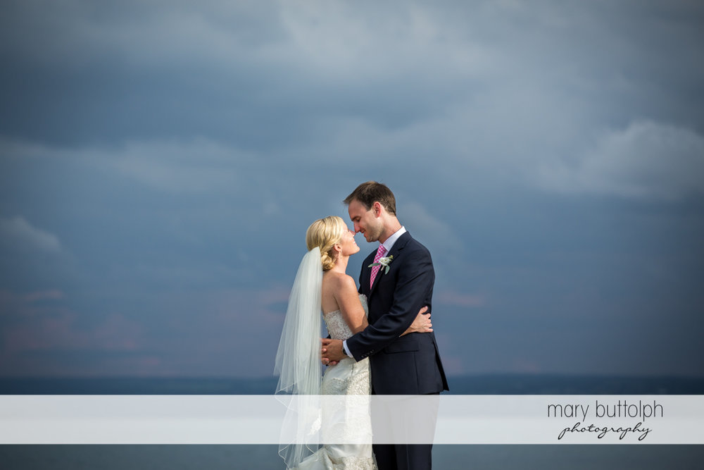 Couple stand by the lake beneath the dark blue sky at Skaneateles Country Club Wedding