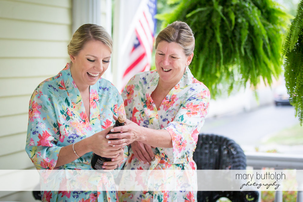 Bride and her mother examine a bottle of wine at Skaneateles Country Club Wedding