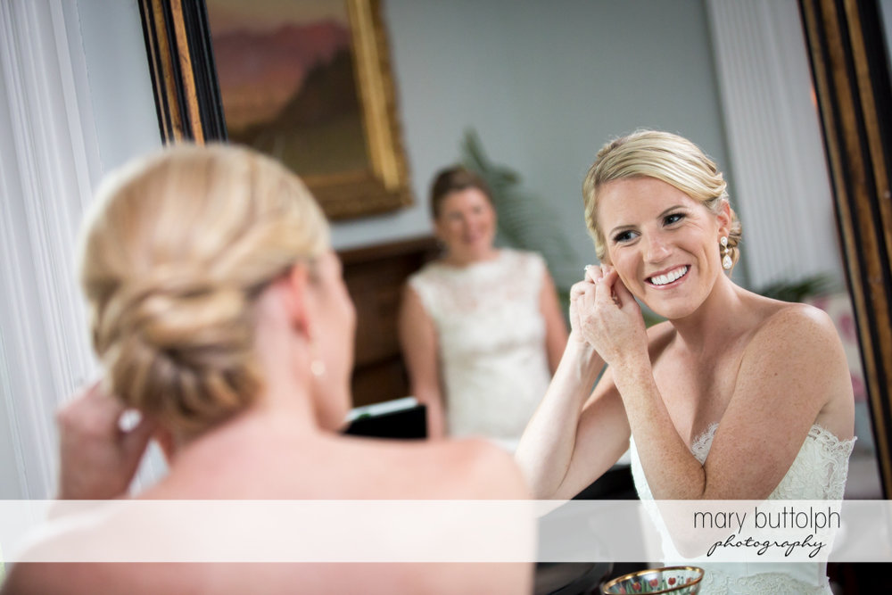 Bride puts on an earring in front of a mirror at Skaneateles Country Club Wedding