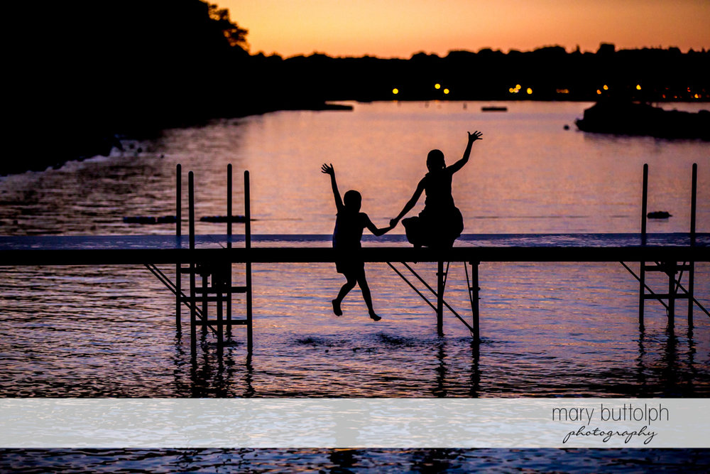 Girls jump into the lake as the sun sets at Skaneateles Country Club