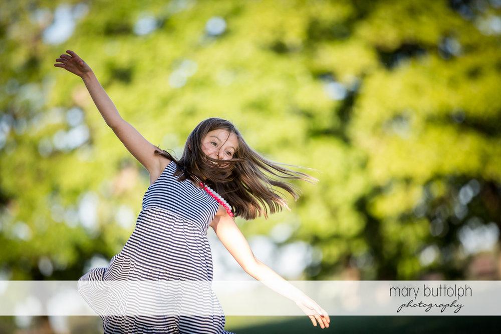 Girl does balancing act near the lake at Skaneateles Country Club