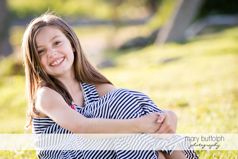 Girl smiles for the camera while sitting on the grass at Skaneateles Country Club