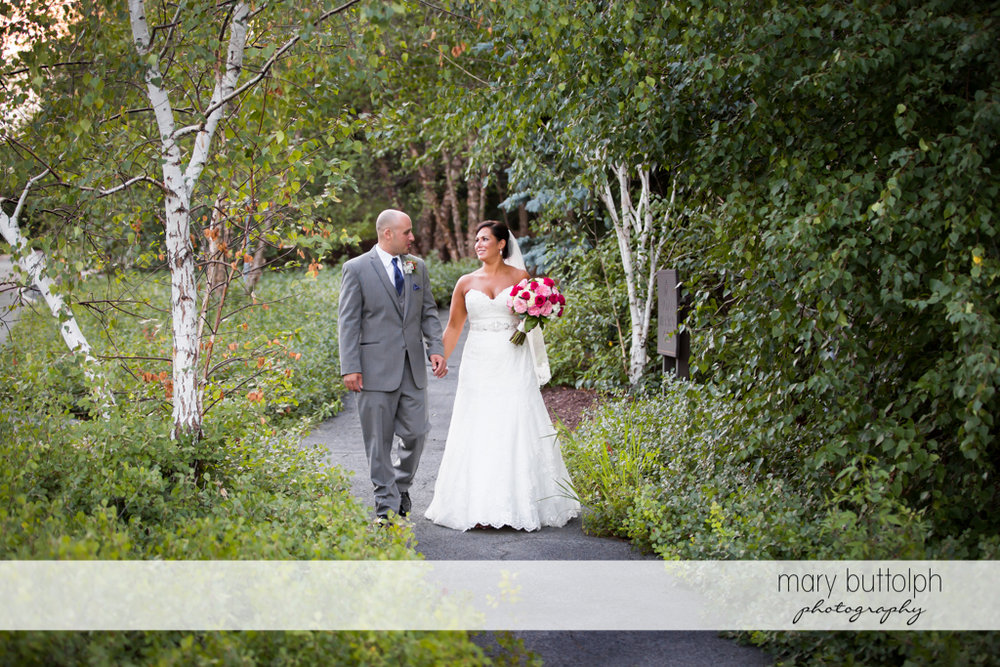 Couple stroll in the woods at The Lodge at Welch Allyn Wedding